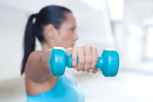 A hand holding blue dumbbell for tricep extension of sporty lady