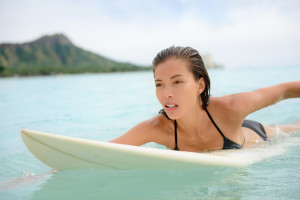 Surfing surfer girl paddle for surf on surfboard. Female bikini