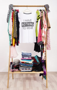 Many Clothes On The Rack With A T-shirt Saying Nothing To Wear.