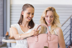 Two happy women looking at handbag in shopping mall